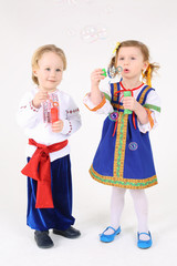 girl and boy in russian folk costumes stand and blow bubbles