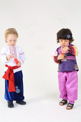 Two little boys in folk costumes stand and blow bubbles on white