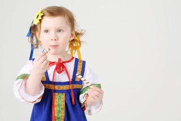 Little girl in russian folk costume eats sweet cookies on white