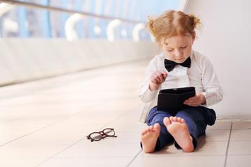 Little cute barefoot girl in white shirt sits on floor