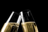 champagne flutes with golden bubbles on black light background poster