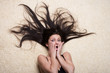 Portrait of a shocked girl with long hair lying on the floor