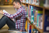 Focused young student sitting on library floor reading