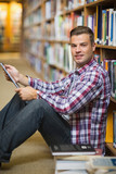 Smiling young student sitting on library floor using tablet