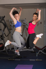 Two fit young women jumping in the gym