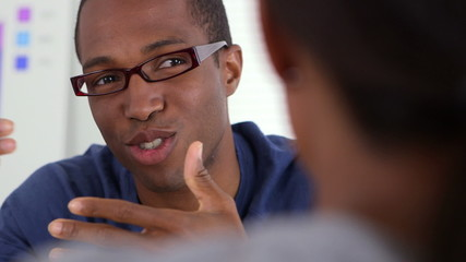 Black businessman talking with coworker in office