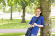 Smiling redhead student leaning against a tree