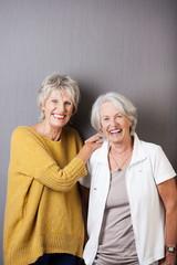 zwei glückliche seniorinnen vor grauer wand
