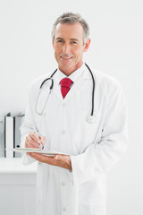 Smiling male doctor writing a report at office