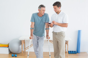 Therapist discussing reports with disabled patient in gym hospit