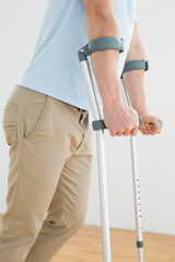 Side view mid section of a man with crutches