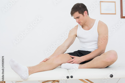 Young man sitting on examination table in medical office