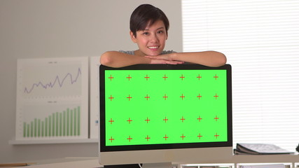 Chinese businesswoman standing by green screen computer