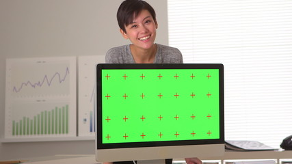 Enthusiastic Chinese businesswoman standing with green screen