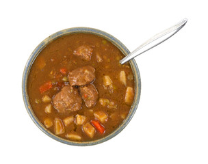 A bowl of meatball stew with a spoon