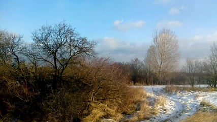 Slow passage through landscape with field and little snow