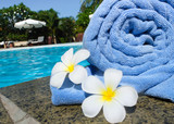 Towel and frangipani flowers beside swimming pool of spa resort