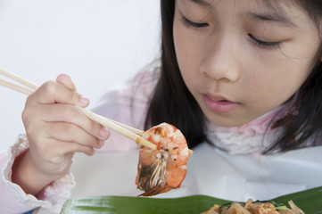 Little Asian girl looking at a shrimp in her chopstick.