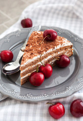 Chocolate cake with cream decorated with fresh cherry