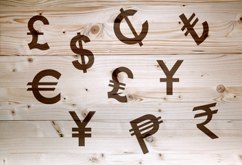 International brown economy currency units on wooden background