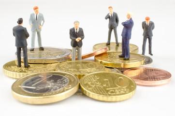Businessmänner auf Geldhaufen