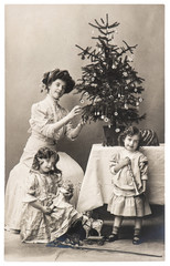 mother and children with christmas tree wearing vintage clothing