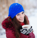 Girl drinking hot tea in the winter forest, close up