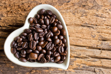 Coffee beans in a cup heart on wooden background