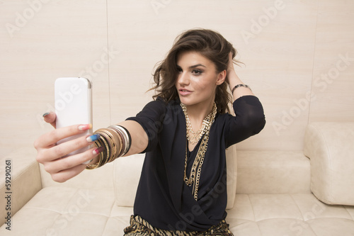 Portrait of beautiwul girl taking photos with cellphone