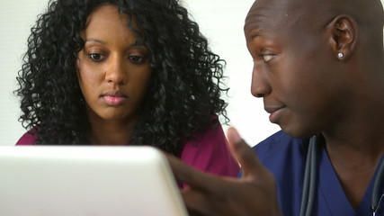 Two African American doctors using laptop together