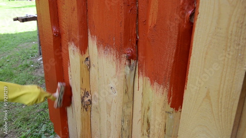 hand yellow glove painting wood plank wall with brush red color