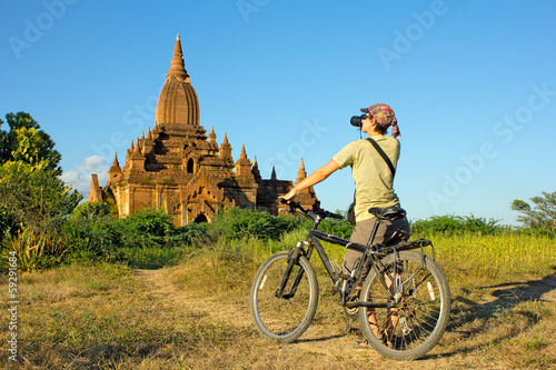 girl photographer on a bicycle takes a picture of the temple in