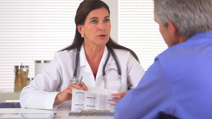 Woman doctor prescribing medication to elderly patient