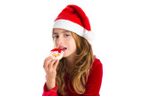 Christmas kid girl eating Xmas Santa cookie