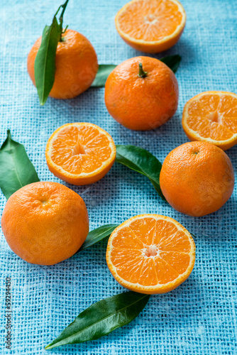 Tangerines with leaves over light blue background