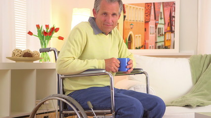 Old man sitting in wheelchair with coffee