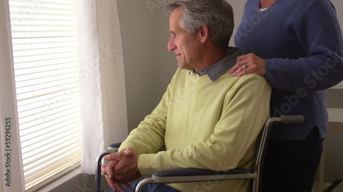 Disabled man sitting by window in wheelchair