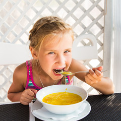 Cute child eating soup
