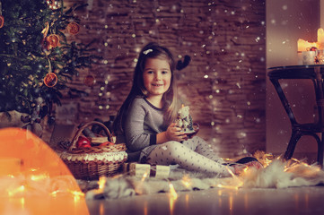 Christmas tree with toys and lights and happy cute little girl