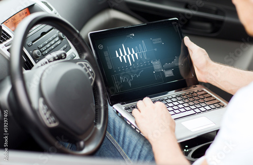 man using laptop computer in car