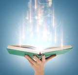 hand holding open book with magic lights