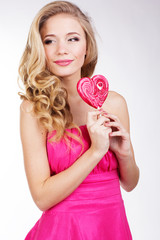 Sexy girl wearing pink dress with candy. Valentine's day