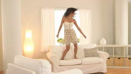 Asian woman jumping on couch and dancing in living room