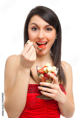 Slim young woman eating fruit salad