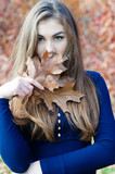 Beautiful woman hiding face behind autumn brown leaf