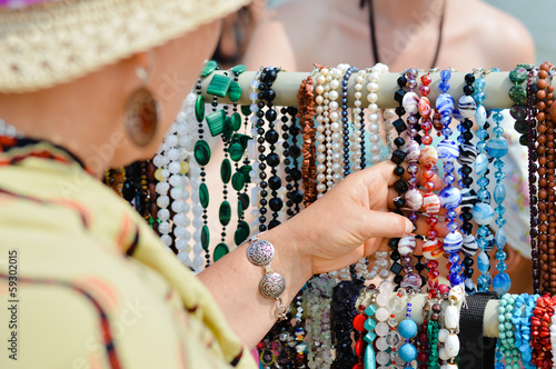 Woman choosing jewelry in row of necklaces and bracelets