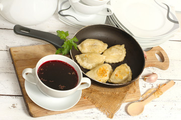 homemade pierogi (ravioli)  and clear red borscht