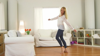 Mature woman jumping on couch and dancing in living room