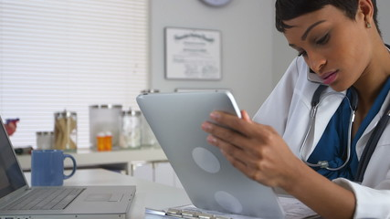 African doctor at desk talking on smartphone