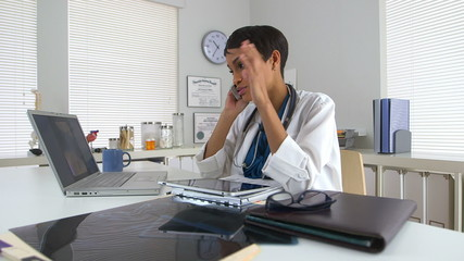 Black doctor at desk talking on smartphone and looking at laptop